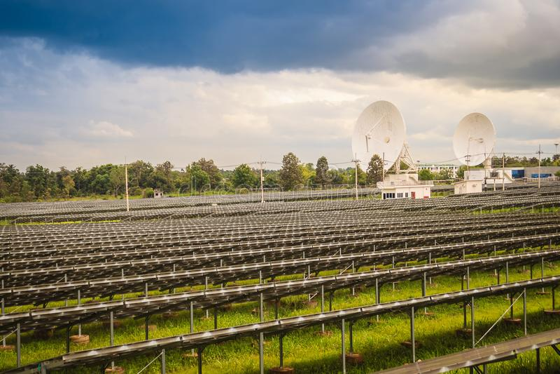 Ηλιακό αγρόκτημα μεγάλων κλιμάκων με τα δορυφορικά πιάτα κάτω από δραματικό στοκ φωτογραφία