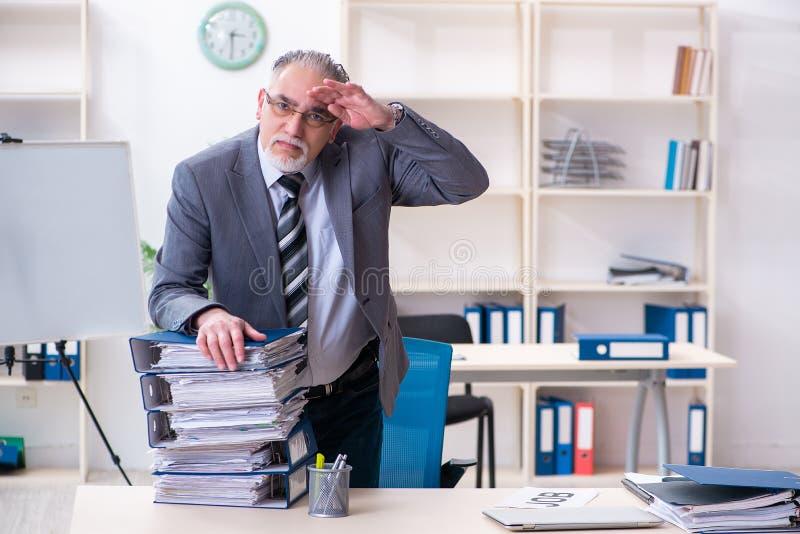 Ηλικίας άνδρας υπάλληλος δυστυχισμένος με την υπερβολική εργασία στοκ εικόνα