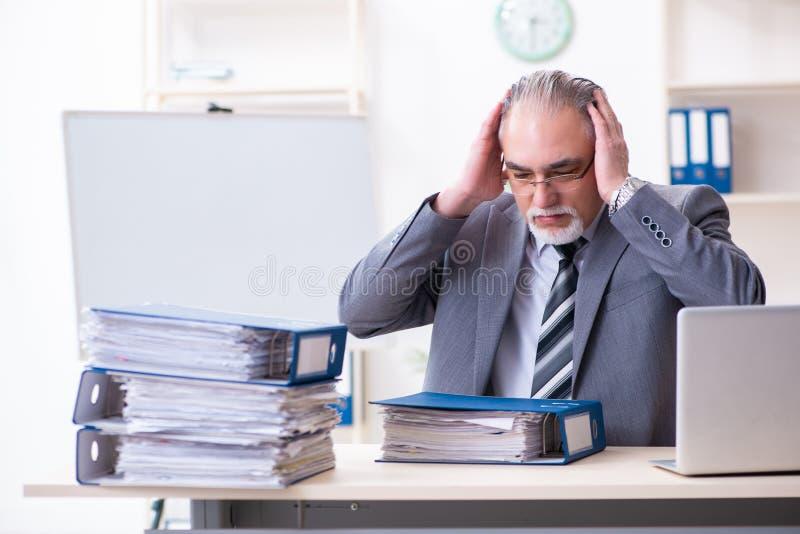 Ηλικίας άνδρας υπάλληλος δυστυχισμένος με την υπερβολική εργασία στοκ εικόνες