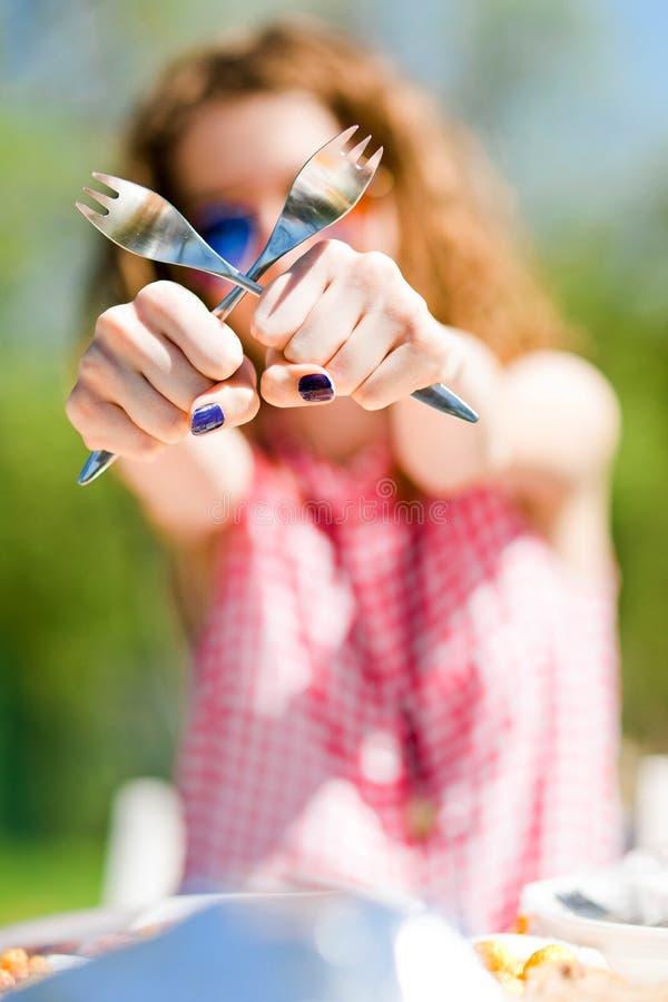 Ηλικίας έφηβος κορίτσι στην κόκκινη ελεγμένη συνεδρίαση πουκάμισων από τον πίνακα στον κήπο στοκ εικόνα
