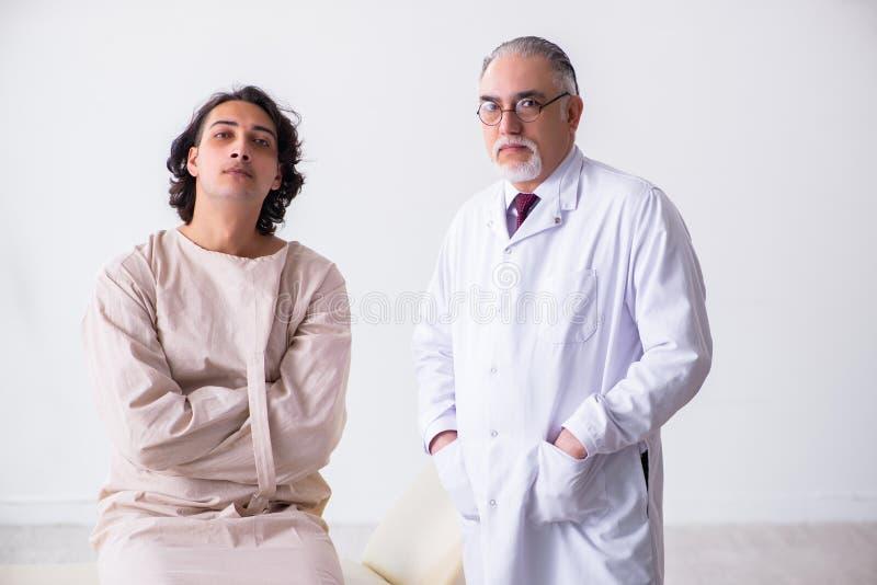 Ηλικίας αρσενικός ψυχίατρος γιατρών που εξετάζει το νέο ασθενή στοκ εικόνα