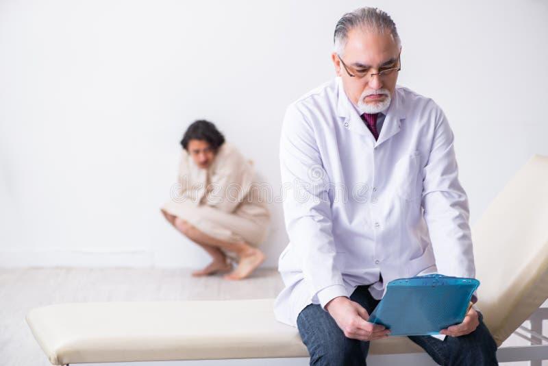 Ηλικίας αρσενικός ψυχίατρος γιατρών που εξετάζει το νέο ασθενή στοκ φωτογραφίες με δικαίωμα ελεύθερης χρήσης