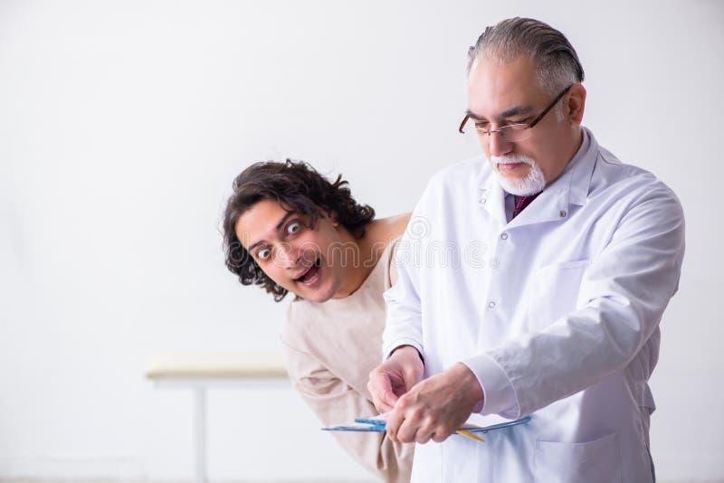 Ηλικίας αρσενικός ψυχίατρος γιατρών που εξετάζει το νέο ασθενή στοκ φωτογραφία