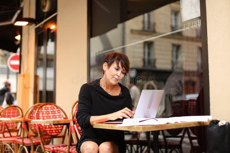 ηλικίας θηλυκό screenwriter που εργάζεται με το σενάριο στο lap-top στοκ εικόνες