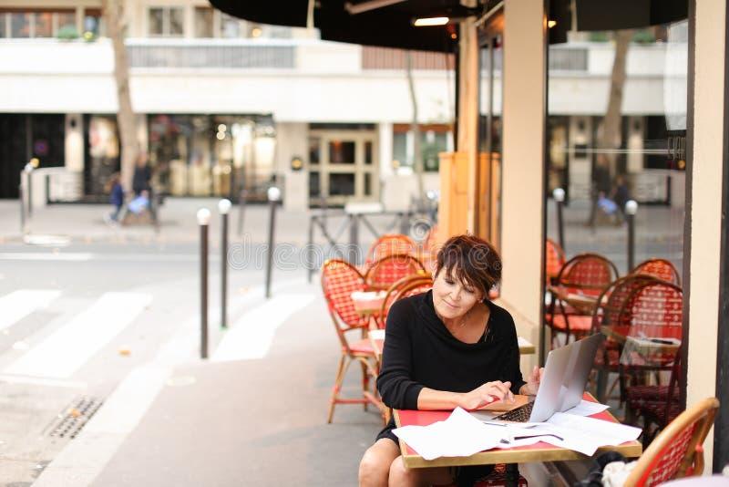 ηλικίας θηλυκό screenwriter που εργάζεται με το σενάριο στο lap-top στοκ φωτογραφίες