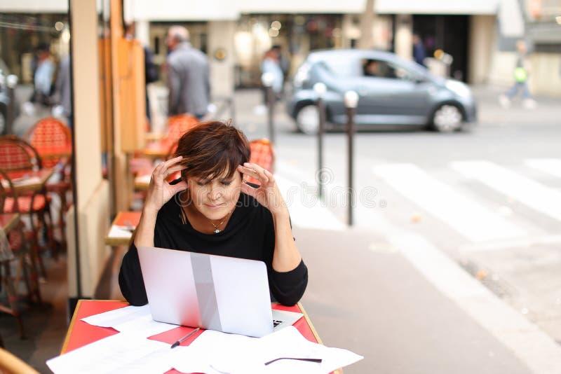 ηλικίας θηλυκό screenwriter που εργάζεται με το σενάριο στο lap-top στοκ εικόνα