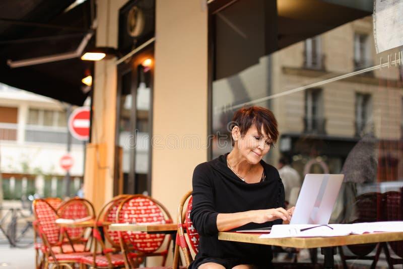 ηλικίας θηλυκό screenwriter που εργάζεται με το σενάριο στο lap-top στοκ εικόνα με δικαίωμα ελεύθερης χρήσης