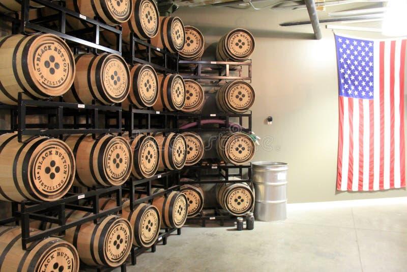 Ηλικίας ξύλινα βαρέλια που συσσωρεύονται στις τοποθετώντας σε ράφι μονάδες μετάλλων, μαύρη οινοπνευματοποιία κουμπιών, Ρότσεστερ, στοκ εικόνες
