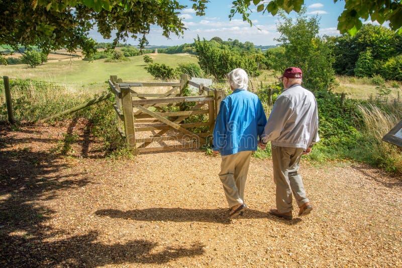 Ηλικιωμένα χέρια λαβής ζευγών, που περπατούν στη βρετανική επαρχία στοκ φωτογραφία με δικαίωμα ελεύθερης χρήσης