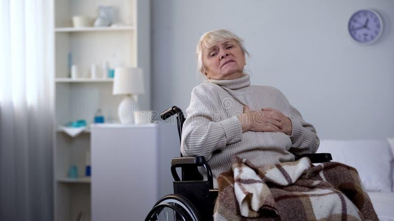 Ηλικιωμένη ανάπηρη γυναίκα που αισθάνεται το θωρακικό πόνο, αρρυθμία καρδιών, υγειονομική περίθαλψη στοκ εικόνες