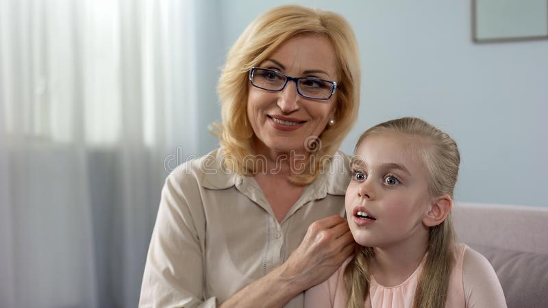 Ηλικιωμένη γιαγιά που ψιθυρίζει το μεγάλο μυστικό στην εντυπωσιασμένη εγγονή της, οικογένεια στοκ φωτογραφία