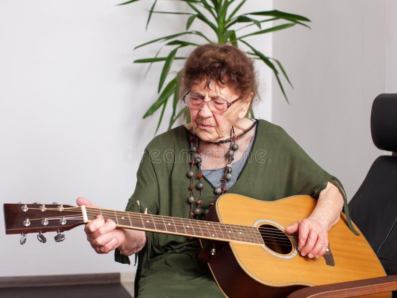 Ηλικιωμένη γυναίκα για να παίξει την κιθάρα στοκ εικόνες
