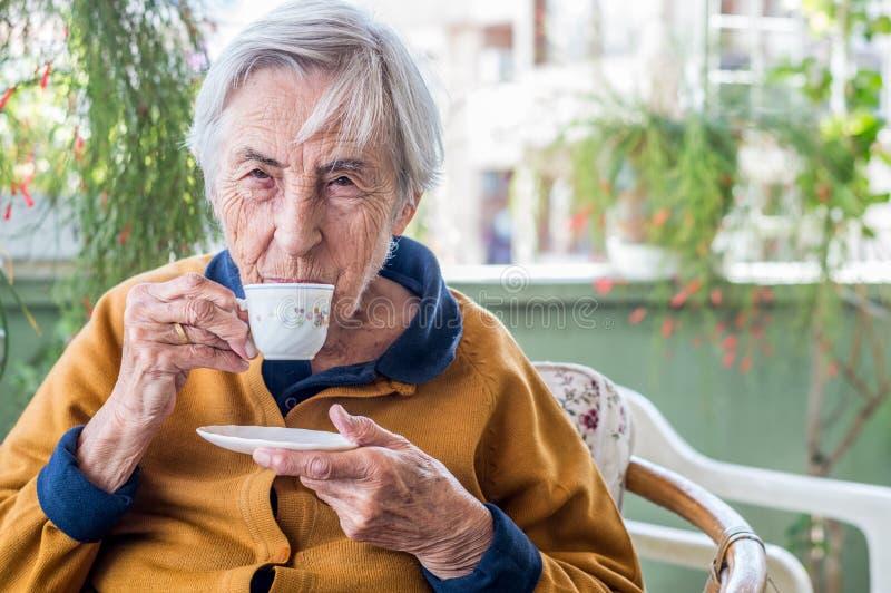 Ηλικιωμένη γυναίκα που κάθεται και που πίνει τον τουρκικό καφέ στο μπαλκόνι μια ηλιόλουστη ημέρα στοκ φωτογραφία