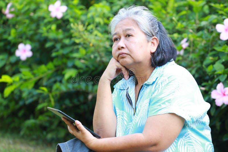 Ηλικιωμένη γυναίκα που κάθεται κενή με μόνη στον κήπο στοκ εικόνες με δικαίωμα ελεύθερης χρήσης