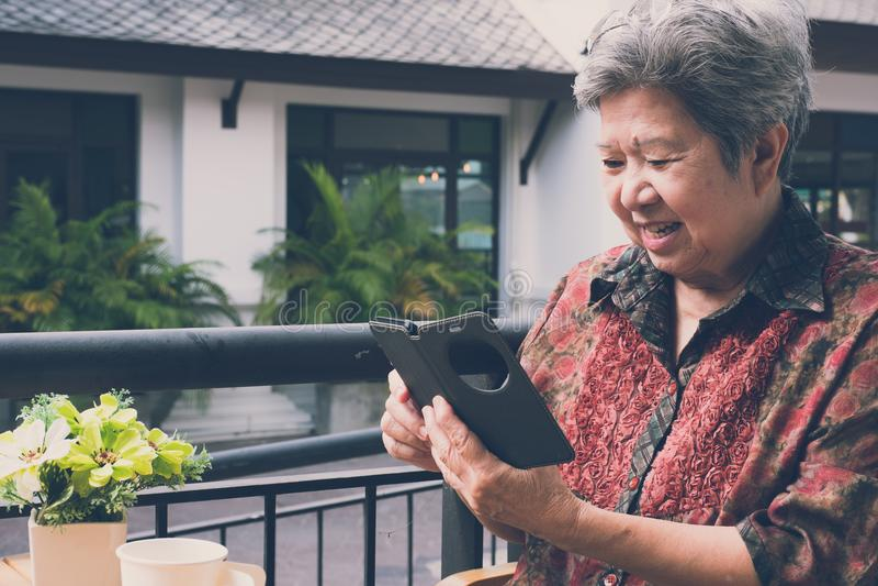 ηλικιωμένη γυναίκα που κρατά το κινητό τηλέφωνο στον καφέ ηλικιωμένο θηλυκό στοκ εικόνες