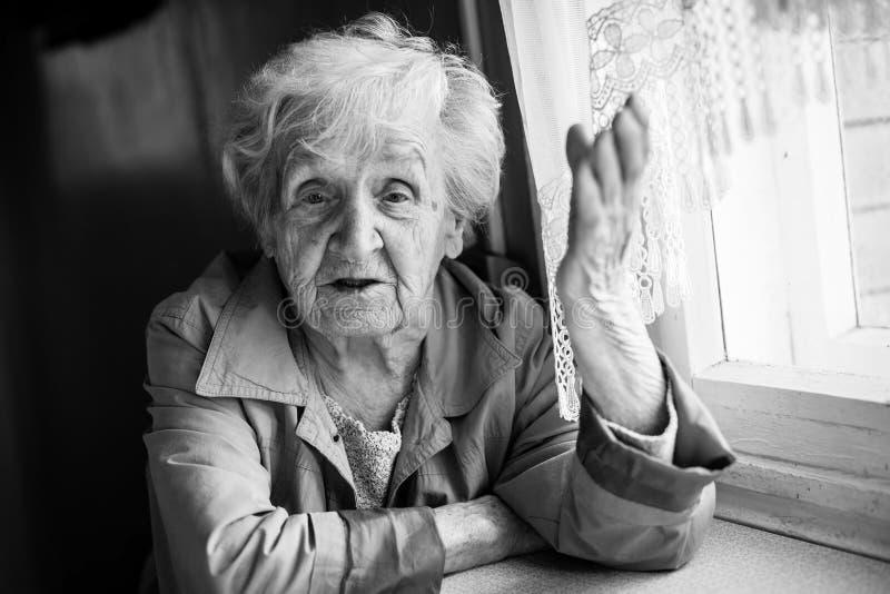 Ηλικιωμένη γυναίκα που μιλά και που καθμένος στον πίνακα grandma στοκ φωτογραφία με δικαίωμα ελεύθερης χρήσης