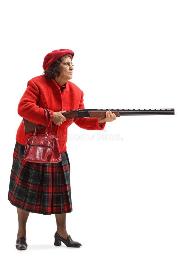 Ηλικιωμένη γυναίκα σε ένα κόκκινο παλτό που κρατά ένα κυνηγετικό όπλο στοκ φωτογραφία