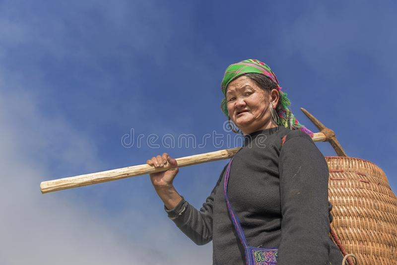 Ηλικιωμένη γυναίκα φυλών Hmong στον τρόπο στον τομέα ορυζώνα της σε Sapa, Βιετνάμ στοκ εικόνα