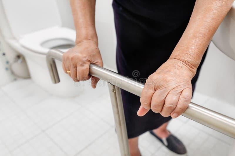 Ηλικιωμένη εκμετάλλευση γυναικών στο κιγκλίδωμα στην τουαλέτα στοκ φωτογραφίες