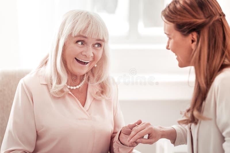 Ηλικιωμένη κομψή γυναίκα με ένα συναίσθημα περιδεραίων που διασκεδάζουν στοκ εικόνα