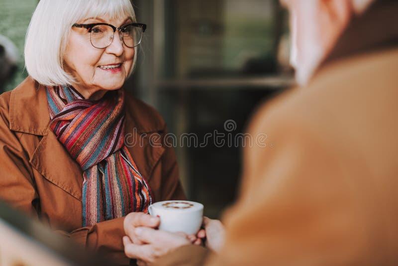 Ηλικιωμένη κυρία με τον καυτό χρόνο εξόδων ποτών με το σύζυγο στον υπαίθριο καφέ στοκ εικόνα με δικαίωμα ελεύθερης χρήσης