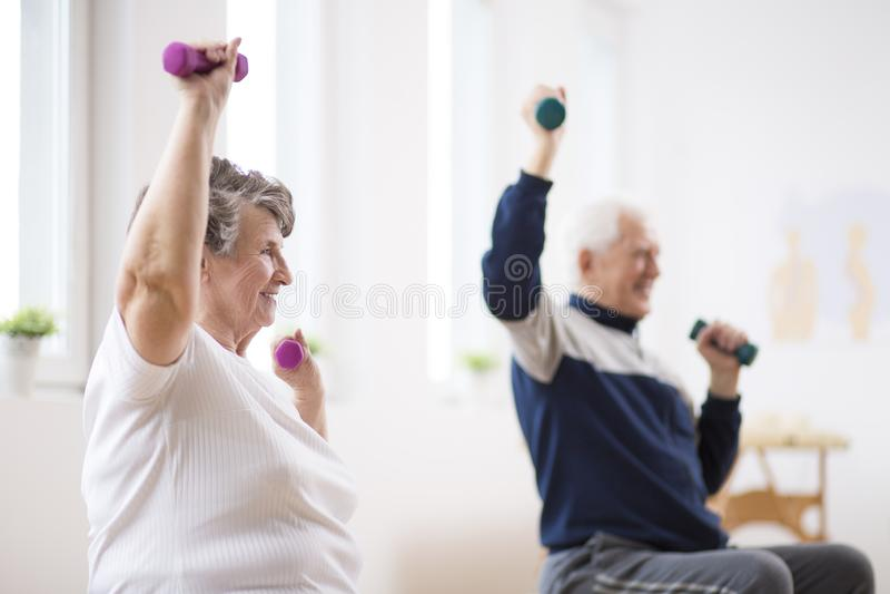 Ηλικιωμένοι άνδρας και γυναίκα που ασκούν με τους αλτήρες κατά τη διάρκεια της συνόδου φυσιοθεραπείας στο νοσοκομείο στοκ φωτογραφίες