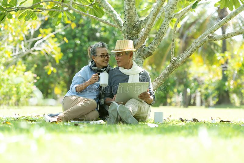 Ηλικιωμένοι ηλικιωμένοι Ασιατικοί Lifestyle συνταξιοδοτούνται, πίνουν καφέ και εργάζονται στο διαδίκτυο στο φυσικό πάρκο, χαρούμε στοκ φωτογραφία με δικαίωμα ελεύθερης χρήσης