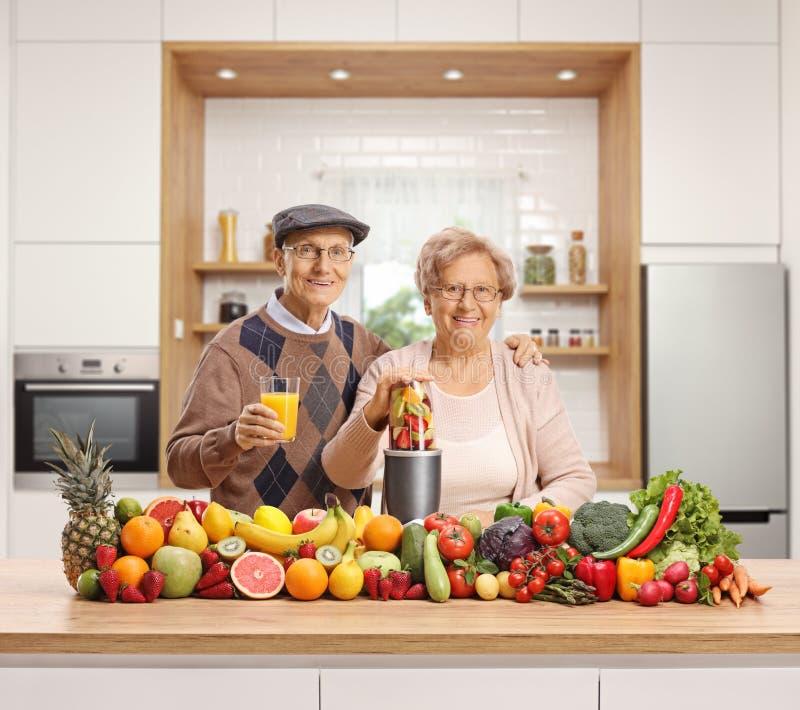 Ηλικιωμένοι σύζυγος και σύζυγος με έναν σωρό των φρούτων και λαχανικών και ενός μπλέντερ στοκ εικόνες με δικαίωμα ελεύθερης χρήσης