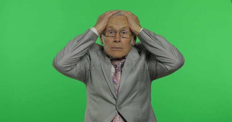 Ηλικιωμένος επιχειρηματίας στα σημεία κοστουμιών σε κάτι με το χέρι του Ανώτερος ηληκιωμένος στοκ φωτογραφία με δικαίωμα ελεύθερης χρήσης