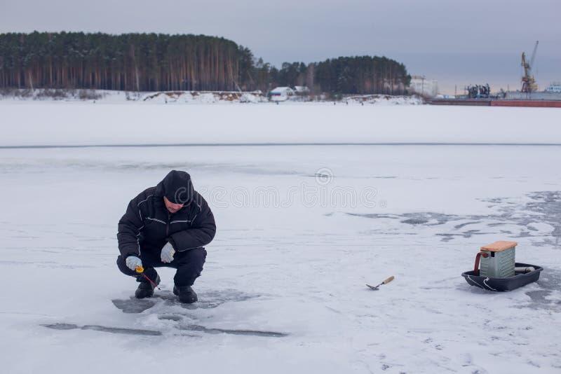 Ηλικιωμένος ψαράς στα σκοτεινά ενδύματα που αλιεύει στη ράβδο χειμερινής αλιείας στον παγωμένο ποταμό στοκ φωτογραφία με δικαίωμα ελεύθερης χρήσης