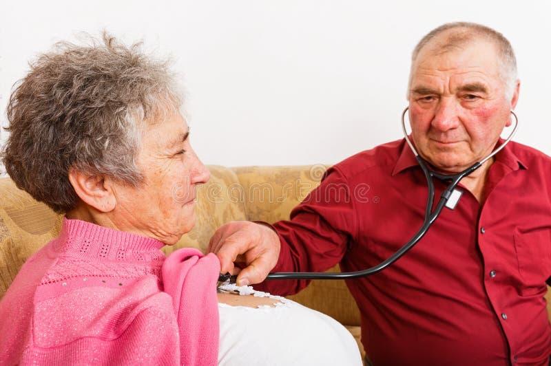 Ηλικιωμένο άτομο που ακούει ο κτύπος της καρδιάς συζύγων του στοκ εικόνες