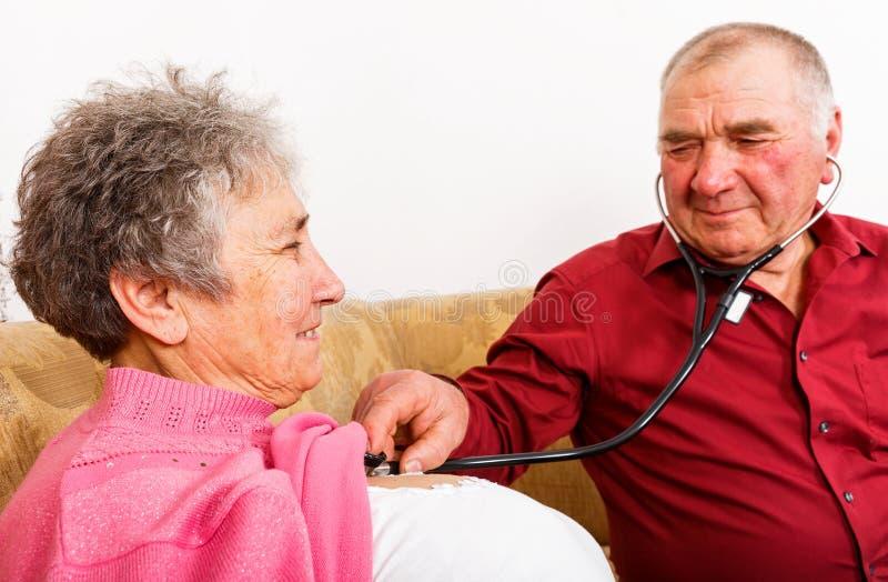 Ηλικιωμένο άτομο που ακούει ο κτύπος της καρδιάς συζύγων του στοκ εικόνα με δικαίωμα ελεύθερης χρήσης