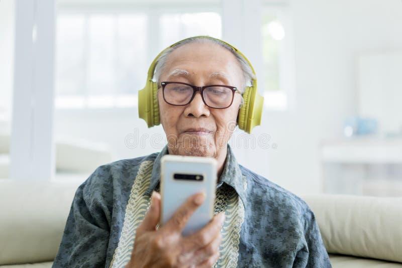 Ηλικιωμένο άτομο που απολαμβάνει τη μουσική με ένα smartphone στοκ φωτογραφίες