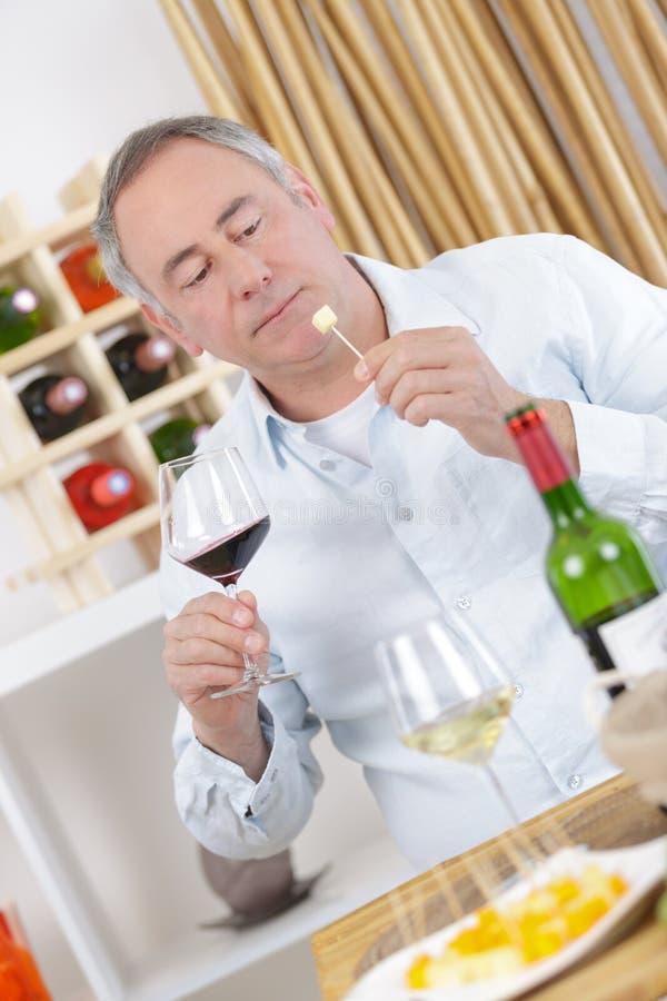 Ηλικιωμένο άτομο που απολαμβάνει το τυρί και το κόκκινο κρασί στο σπίτι στοκ φωτογραφία με δικαίωμα ελεύθερης χρήσης