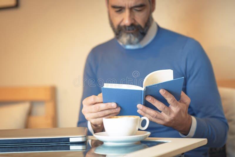 Ηλικιωμένο άτομο που διαβάζει ένα βιβλίο σε μια καφετερία στοκ εικόνα με δικαίωμα ελεύθερης χρήσης