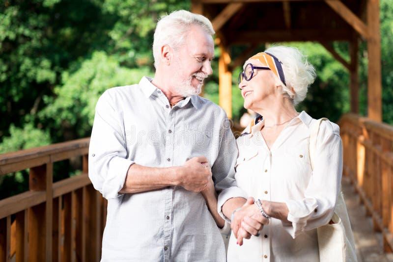 Ηλικιωμένο γενειοφόρο άτομο που χαμογελά κρατώντας το χέρι της συζύγου του στοκ φωτογραφίες