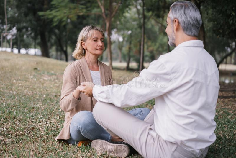Ηλικιωμένο ζευγάρι που εξασκεί τη γιόγκα ενώ κάθεται να κάνει παρέα στο δημόσιο πάρκο Έννοια της χαλάρωσης και του διαλογισμού στοκ εικόνες