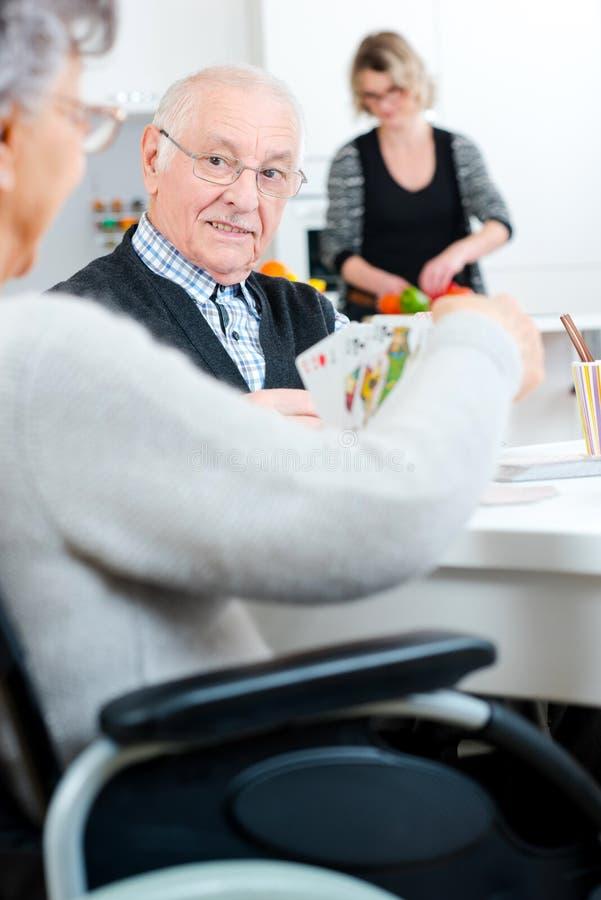 Ηλικιωμένο ζεύγος με την κόρη που προετοιμάζει το γεύμα στοκ εικόνες