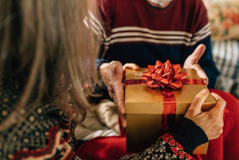 Ηλικιωμένο ζεύγος που ανταλλάσσει τα δώρα στοκ φωτογραφία με δικαίωμα ελεύθερης χρήσης