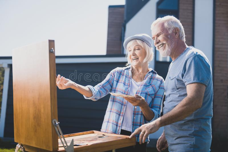 Ηλικιωμένο ζεύγος που γελά σύροντας ακόμα τη ζωή στον κήπο τους από κοινού στοκ εικόνες