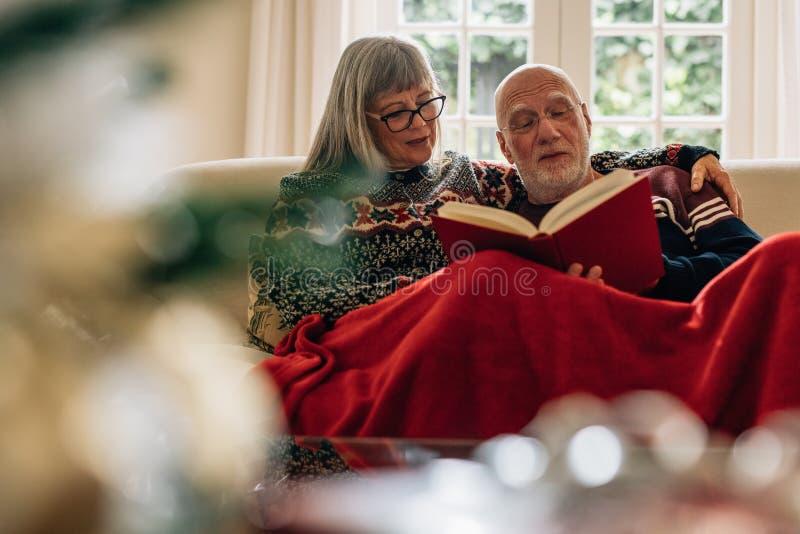 Ηλικιωμένο ζεύγος που διαβάζει μια συνεδρίαση βιβλίων στον καναπέ στο σπίτι στοκ φωτογραφίες