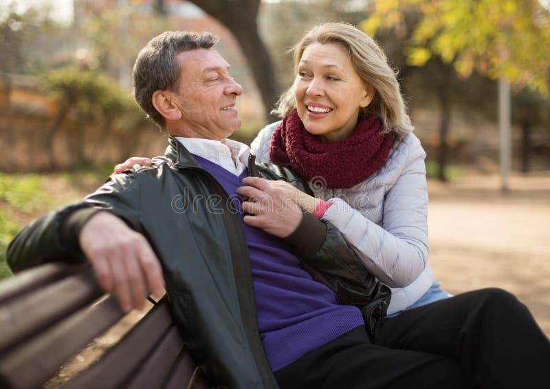 Ηλικιωμένο ζεύγος σε έναν πάγκο στο πάρκο στην ημέρα φθινοπώρου στοκ εικόνα