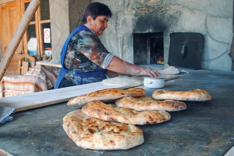 Ηλικιωμένο ψωμί ψησίματος γυναικών σε έναν φούρνο στοκ φωτογραφία