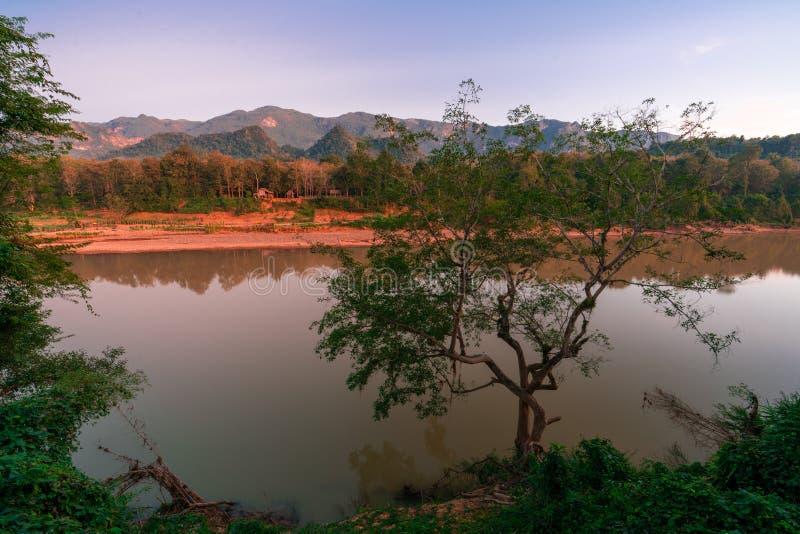 Ηλιοβασίλεμα έξω από Luang Prabang Αντικνήμια ήλιων σε ένα παλαιό χωριό Ζούγκλα γύρω από το χωριό Khan ποταμός Nam μπροστά από το στοκ εικόνα με δικαίωμα ελεύθερης χρήσης