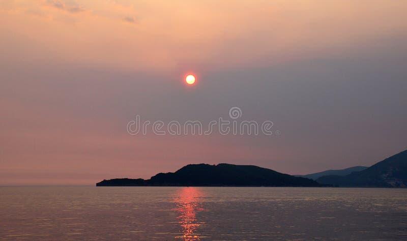 Ηλιοβασίλεμα θάλασσας πέρα από τη δύσκολη ακτή στοκ εικόνα με δικαίωμα ελεύθερης χρήσης