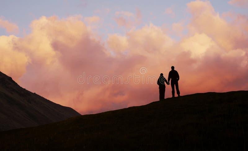 ηλιοβασίλεμα κοριτσιών αγοριών ανασκόπησης στοκ φωτογραφία