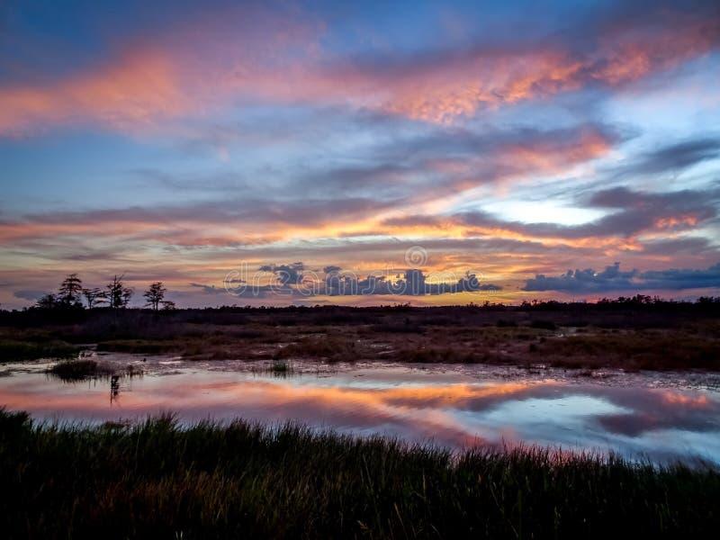 ηλιοβασίλεμα με τα ρόδινα σύννεφα στον ποταμό ελών στοκ φωτογραφία