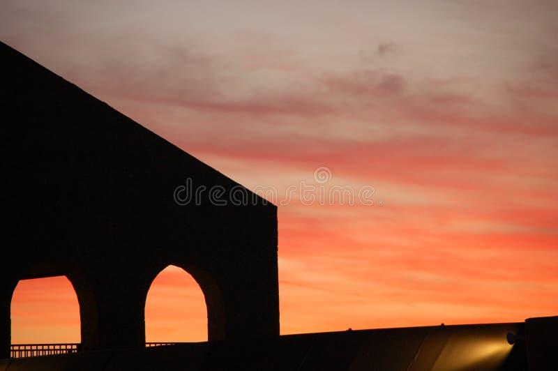 Ηλιοβασίλεμα με τη σκιαγραφία της δομής με τις αψίδες στοκ εικόνα με δικαίωμα ελεύθερης χρήσης