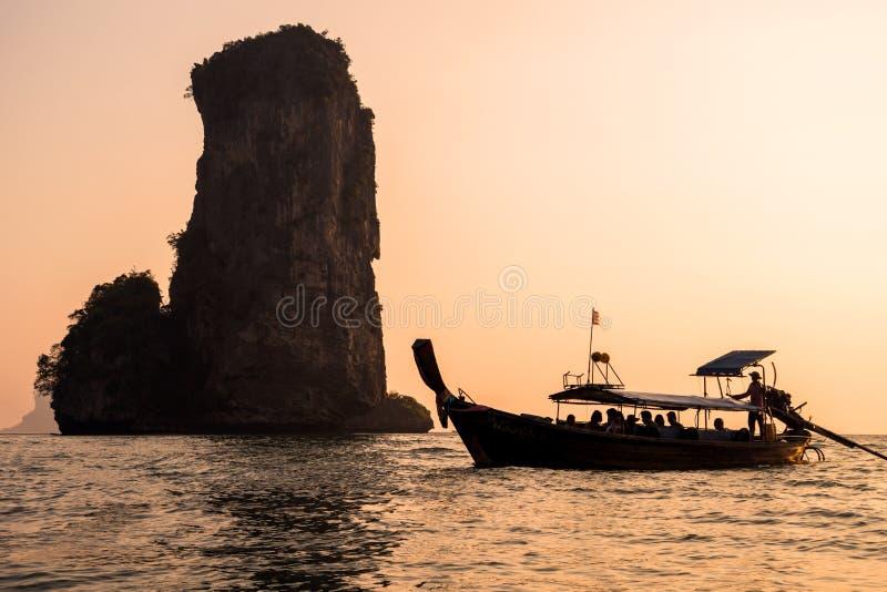 Ηλιοβασίλεμα με τη σκιαγραφία της παραδοσιακής βάρκας Longtail και του υψηλού βράχου στη θάλασσα Ταϊλάνδη στοκ εικόνα