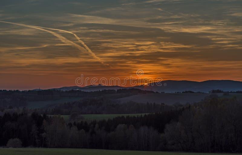 Ηλιοβασίλεμα με το λόφο Jested κοντά στο χωριό Roprachtice στοκ εικόνα